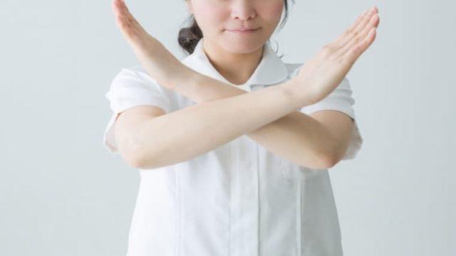 ダメを表すジェスチャーをする看護師の画像