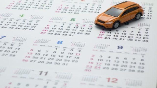 カレンダーの上を走る車。連休ドライブをイメージした画像